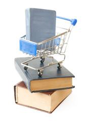 Shopping cart on books isolated on white