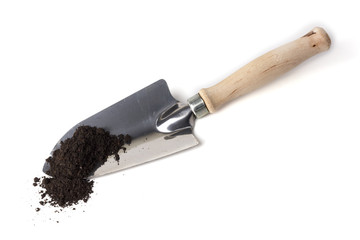 Gardening spade in soil isolated on white