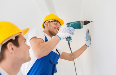 group of smiling builders with drill indoors