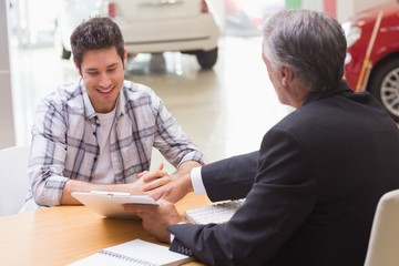 Salesman showing client where to sign the deal