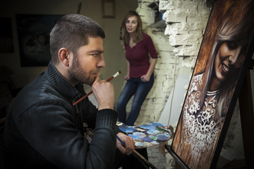 Young artist in his studio working on a portrait