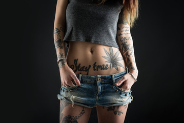 Close up of beautiful woman with tattoo wearing jeans short pain