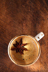 A cup of spiced coffee with anis star and cinamon sticks and sug