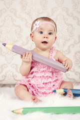 Little baby girl holding big crayon