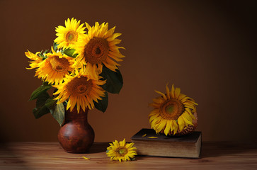 Sunflower in a ceramic vase, books and wicker basket