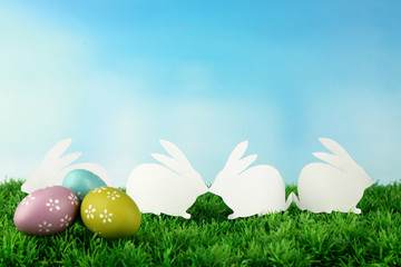 Paper Easter rabbits and eggs on green grass, on sky background