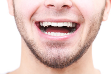 Smiling man after visit dentist isolated on white