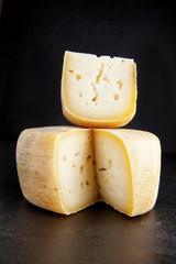 Cheese wheel on dark. Italian parmesan. Pecorio cheese.
