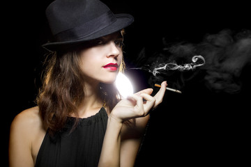 young female in stylish hat smoking a lit cigarette