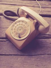 Retro rotary telephone on wood background.