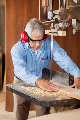 Carpenter Using Bandsaw To Cut Wooden Plank
