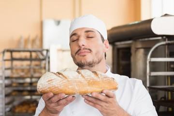 Baker smelling freshly baked loaf