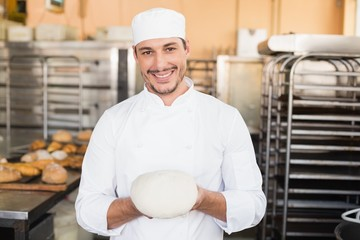 Smiling baker holding raw dough