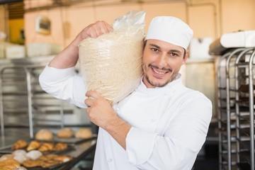 Smiling baker holding bag of rising dough
