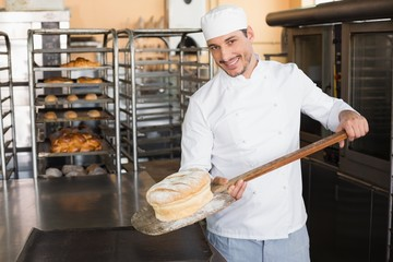 Happy baker taking out fresh loaf