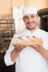 Baker holding freshly baked loaf