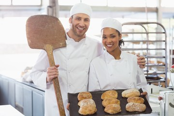 Team of bakers smiling at camera with trays of loaves