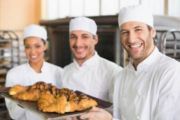 Team of bakers smiling at camera with trays of croissants