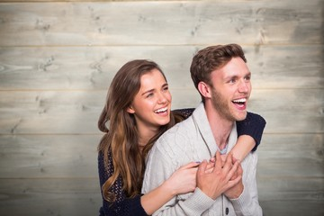 Composite image of cheerful young couple embracing
