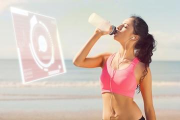 Beautiful healthy woman drinking water on beach