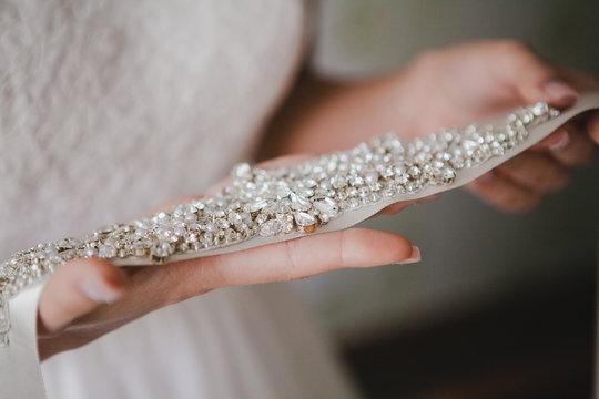 Bride holding a belt with rhinestones. wedding accessories