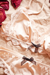 Tenderness peachys lingerie with candle and dry petals.