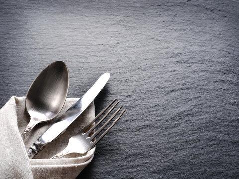 Silver cutlery on a dark grey background.