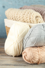 Knitting clothes and yarn in basket, on wooden background