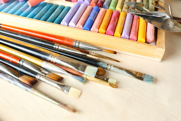 Paintbrushes with colorful chalk pastels in box