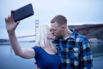 couple kissing in front of golden gate bridge and taking selfie