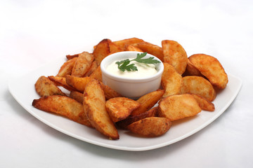 Fried potato wedges with white sauce on white plate