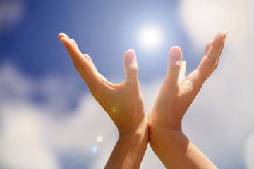 Hands holding light on the blue sky