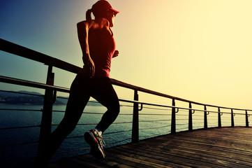 young fitness woman running on sunrise seaside boardwalk