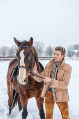 the girl next door with a horse in the winter on snow