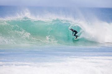 Surfer riding large turquoise wave