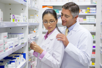 Pharmacist placing hand on colleagues shoulder in pharmacy