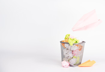 isolated wastebasket full of waste paper and paper airplane