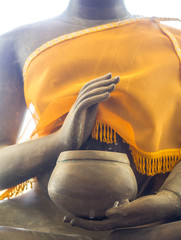 Hands of Buddha statue in posture of begging with alms bowl