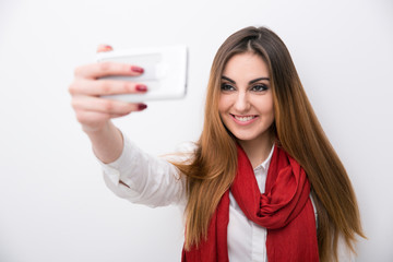 Smiling woman making photo on smartphone