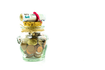 Money - coins and banknotes - in a jar on white background