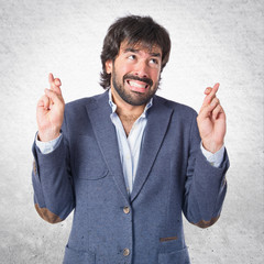 Man with his fingers crossing over white background