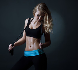 Sport  blond woman with skipping rope and strong abc.