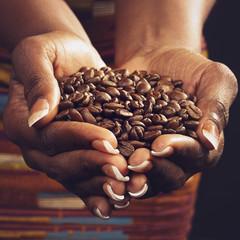 Foto op Plexiglas koffiebar femme noire tenant café en grains