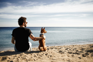 Caucasian man in sunglasses sitting in beach with friend's dog