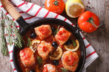 fish in tomato in a pan and ingredients horizontal top view