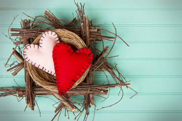 Two felt hearts in a rustic wooden nest