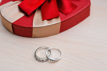 two wedding rings on a wooden background
