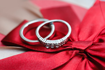 two wedding rings on red background