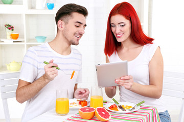 Happy couple has breakfast in kitchen