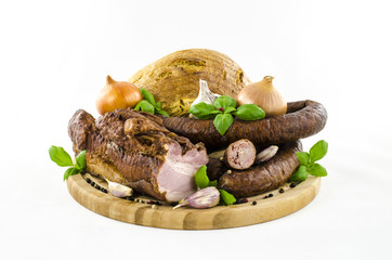 Bacon and sausage with vegetables and bread on wooden board